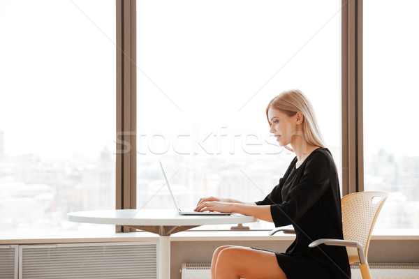 Cheerful young woman worker using laptop computer Stock photo © deandrobot