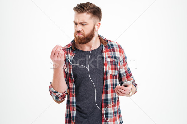 Upset irritated young man listening to music with smartphone Stock photo © deandrobot