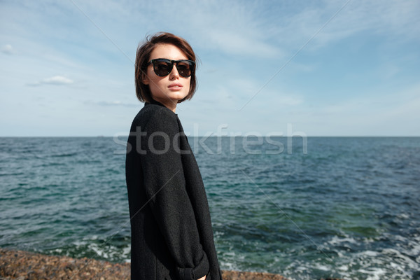 Woman in sunglasses and black coat on the seaside Stock photo © deandrobot