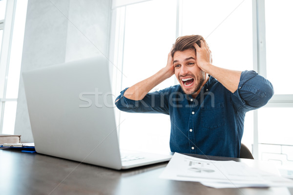 Shocked man holding head with hands while looking at laptop Stock photo © deandrobot