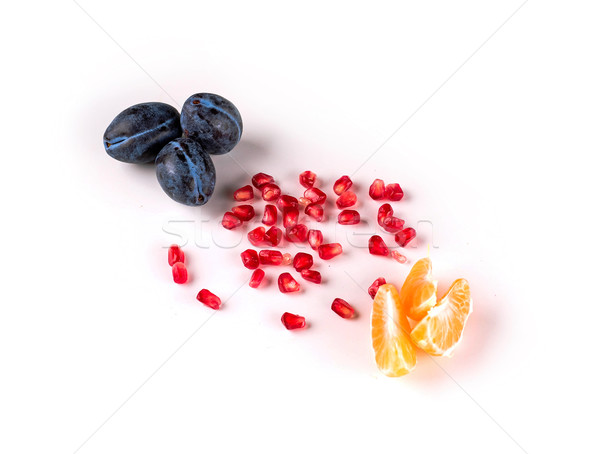 Top view of fresh plums, peeled tangerines and pomegranate seeds Stock photo © deandrobot