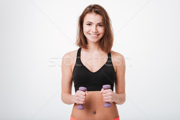 Smiling young fitness lady make exercises with dumbbells Stock photo © deandrobot