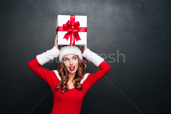 Woman in red dress holding gift box above her head Stock photo © deandrobot