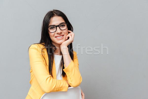 Bájos hölgy ül szürke néz kamerába Stock fotó © deandrobot