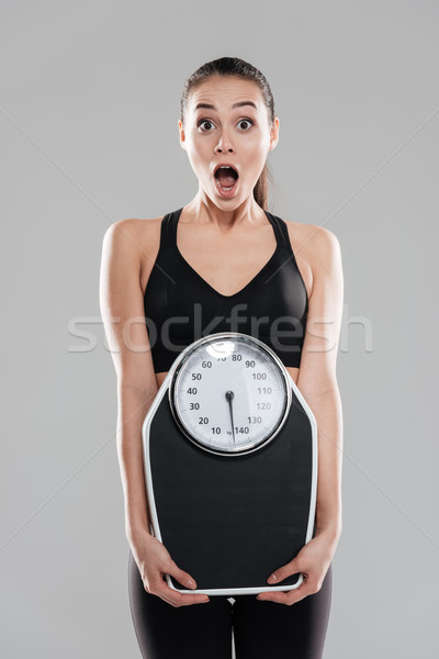 Shocked astonished young woman athlete holding weighing scale Stock photo © deandrobot