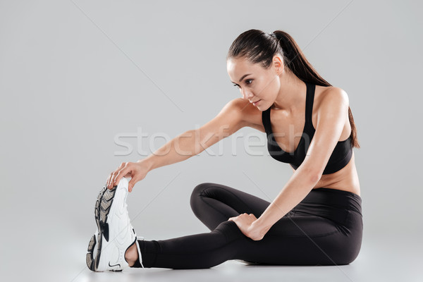 Pretty young sportswoman sitting and stretching legs Stock photo © deandrobot