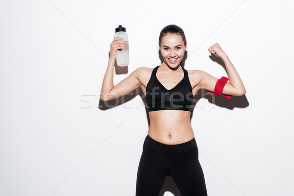 Happy young woman athlete with bottle of water showing biceps Stock photo © deandrobot