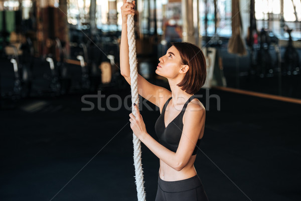 Fitness woman climbing on the rope in gym Stock photo © deandrobot