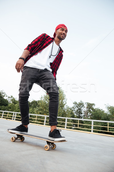 Attractive dark skinned man skateboarding Stock photo © deandrobot