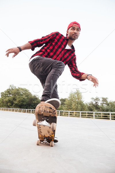 Young dark skinned guy skateboarding Stock photo © deandrobot