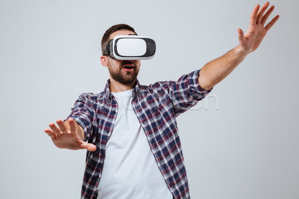 Bearded man in shirt using virtual reality device Stock photo © deandrobot