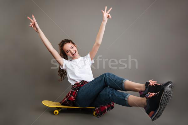 Derűs lány tinédzser ül gördeszka mutat Stock fotó © deandrobot