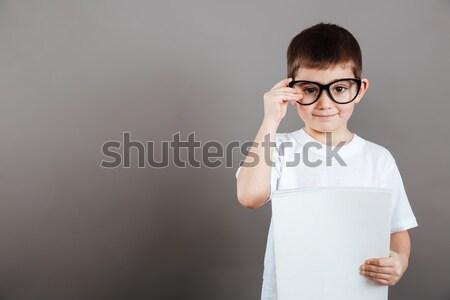 Aranyos kicsi fiú szemüveg tart fehér Stock fotó © deandrobot