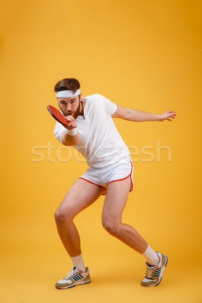 Concentrated young sportsman holding racket for table tennis Stock photo © deandrobot