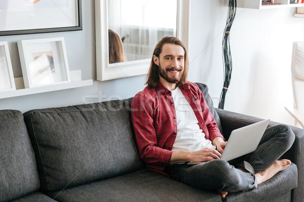 Alegre barbudo moço usando laptop sofá casa Foto stock © deandrobot