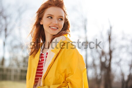 Portrait of a smiling red hair woman in coat walking Stock photo © deandrobot