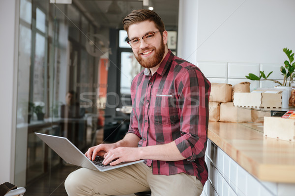 Sorridere barbuto giovane occhiali utilizzando il computer portatile seduta Foto d'archivio © deandrobot