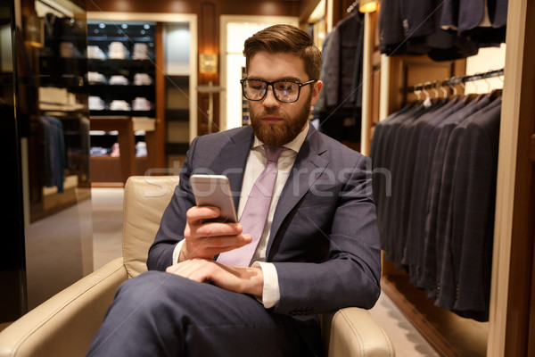 Concentrated young bearded businessman sitting indoors chatting Stock photo © deandrobot