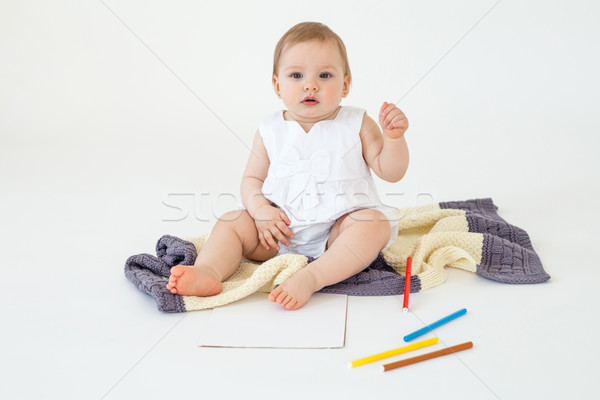 Pretty little girl sitting on floor on plaid holding markers Stock photo © deandrobot