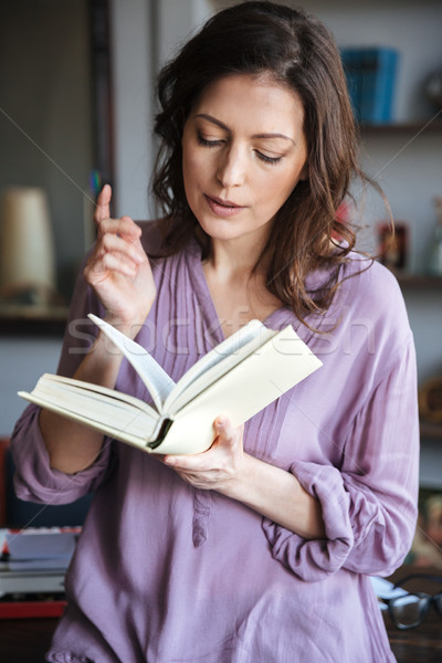Portrait of a woman reading book indoors Stock photo © deandrobot