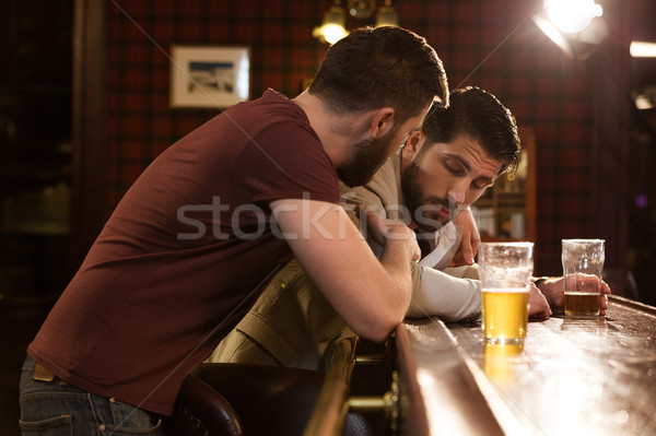 Young man talking to his drunk friend Stock photo © deandrobot