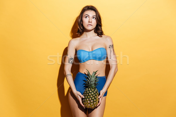Pretty young woman in swimwear holding pineapple Stock photo © deandrobot