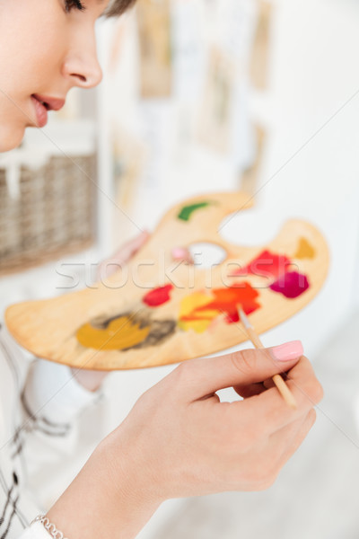 Female artist holding palette and mixing paint colors in studio Stock photo © deandrobot