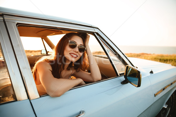 Stock photo: Happy young woman in sunglasses leaning on a window