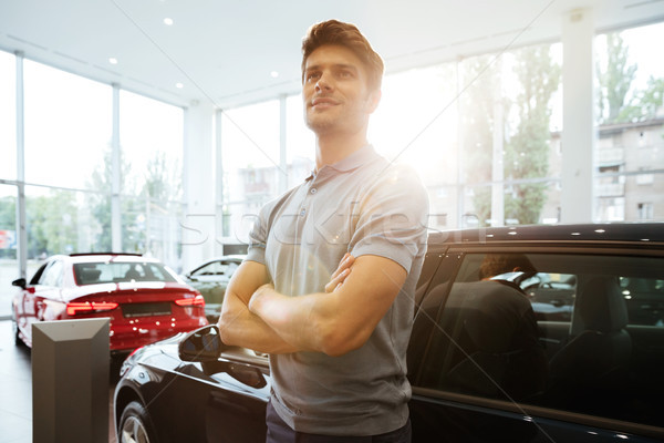 Stock photo: Handsome happy man standing in front of a car