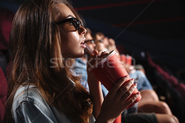 Lady sitting in cinema watch film drinking aerated sweet water. Stock photo © deandrobot