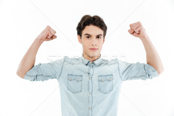 Portrait of a handsome young guy flexing bicep muscles Stock photo © deandrobot