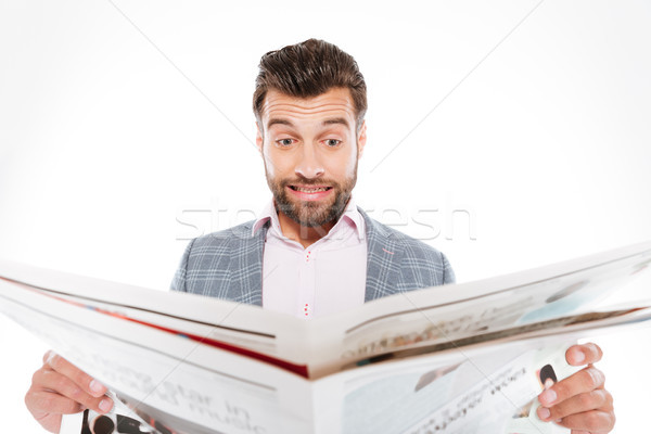 Confused young man reading gazette Stock photo © deandrobot