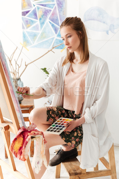 Beautiful young caucasian lady painter at workspace Stock photo © deandrobot