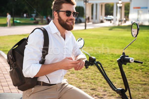 Vista laterale sorridere barbuto uomo occhiali da sole seduta Foto d'archivio © deandrobot