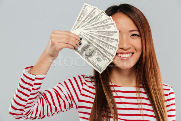 Smiling asian woman in sweater is covering in money Stock photo © deandrobot