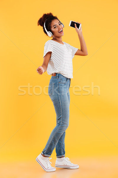 Full-length image of pleased african woman dancing and listening music Stock photo © deandrobot