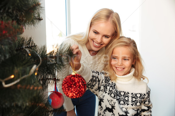 Happy little girl decorating christmas tree with her mother at h Stock photo © deandrobot