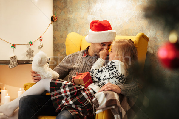 Little blonde kid tweaks her fathers nose while sitting on his k Stock photo © deandrobot