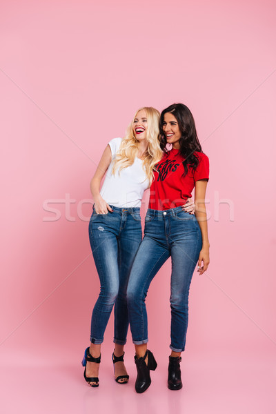 Happy cheerful ladies looking aside and laughing isolated over pink Stock photo © deandrobot