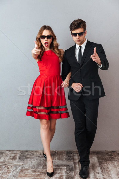 Full length portrait of a young couple dressed in formal wear Stock photo © deandrobot