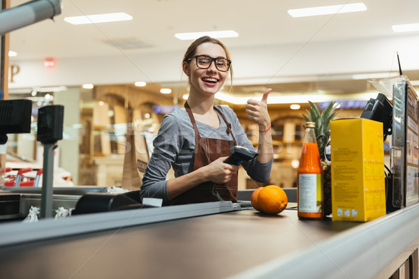 Pretty female cashier scanning grocery items Stock photo © deandrobot