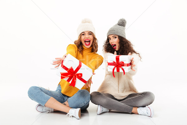 Two screaming girls in sweaters and hats sitting with gifts Stock photo © deandrobot
