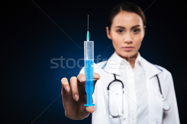 Close up of young doctor holding syringe isolated Stock photo © deandrobot