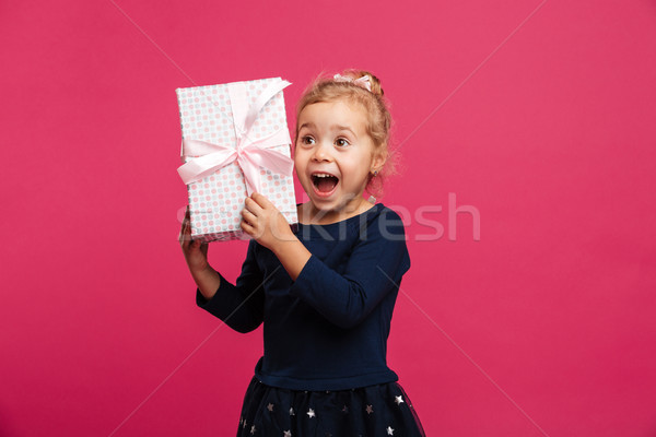 Cheerful young blonde girl holding gift box and rejoices Stock photo © deandrobot