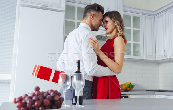 Smiling delightful lady hugging her man while he hiding gift for her Stock photo © deandrobot