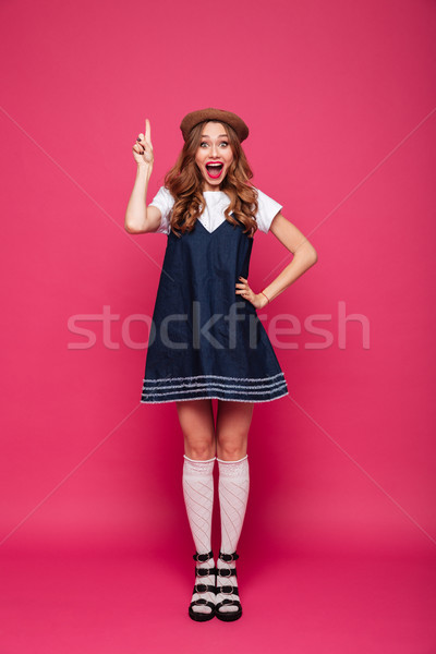 Beautiful happy woman holding finger up while have an idea isolated Stock photo © deandrobot