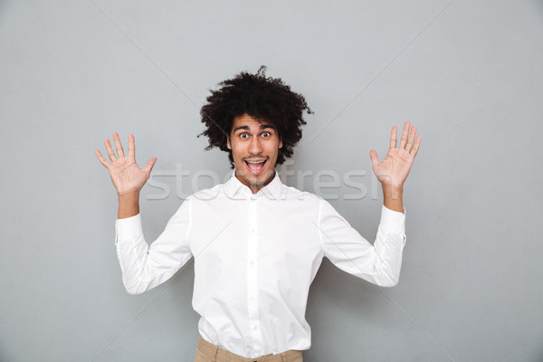 Portrait of a cheery young african man holding hands raised Stock photo © deandrobot