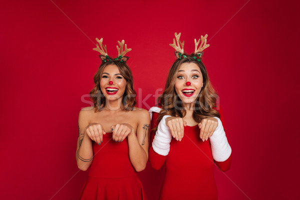 Funny young women friends wearing christmas deer costumes Stock photo © deandrobot