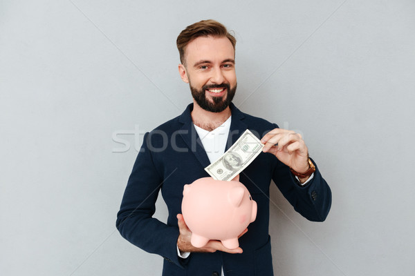Young bearded man looking camera while put money in money-box Stock photo © deandrobot