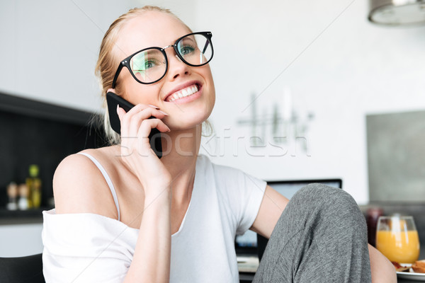 Cheerful lady in glasses smiling and talking on smartphone in kitchen Stock photo © deandrobot